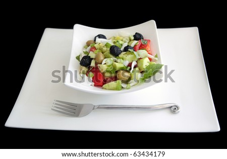 Greek salad: simple greek salad with green and black olives, cucumber, tomatoes, herbs on square white dishware shot on black background - stock photo