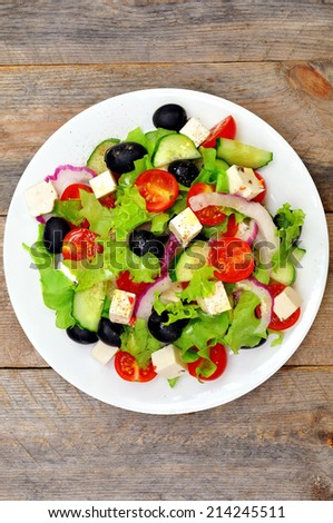 Greek salad (top view) on a wooden table - stock photo