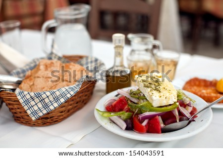 Greek salad with country bread and home made white wine   - stock photo