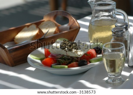 greek salad with country bread and home made white wine taverna setting - stock photo