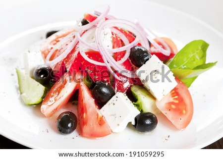 Greek salad with cucumbers, tomatoes, feta cheese, olives, sweet pepper and onions - stock photo