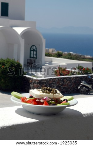 greek salad with cycladic architecture in background over aegean sea - stock photo