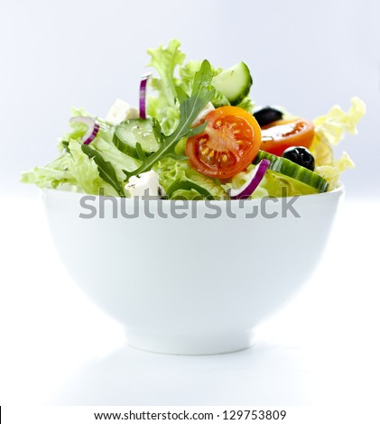 Greek salad with feta, cherry tomatoes, olives, cucumber in a white bowl