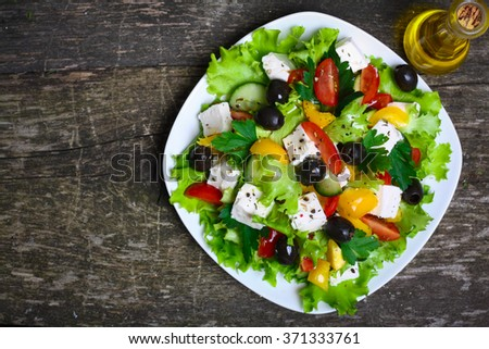 Greek salad with fresh vegetables, feta cheese and black olives on a wooden background - stock photo