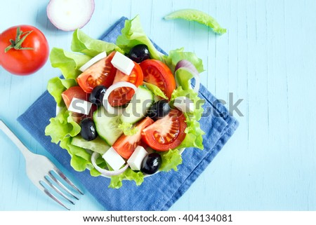 Greek salad with fresh vegetables, feta cheese and black olives over blue background