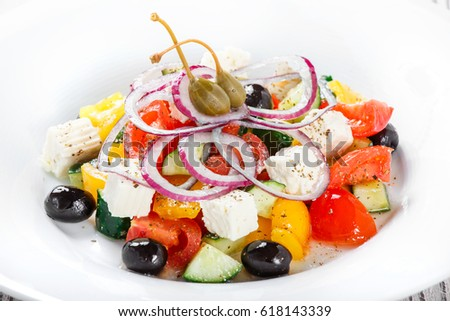 Greek salad with fresh vegetables, olives and feta cheese on wooden background close up. Top view