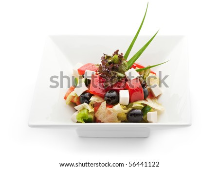 Greek Salad with Tomatoes, Cubed Feta Cheese, Olives, Cucumber and other Vegetables - stock photo