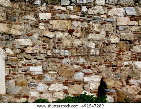 greek stone wall with elements of ancient pieces