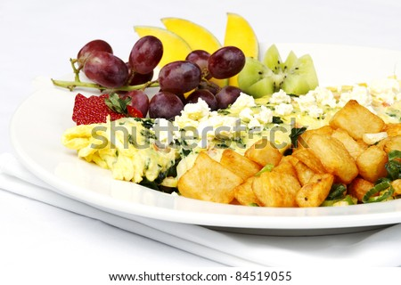 Greek style omelet with assorted fruits and hash browns - stock photo