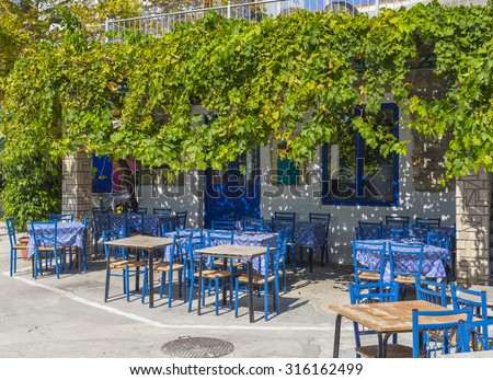 Greek tavern, viney, leaves,  blue tables and chairs, Parga town - stock photo
