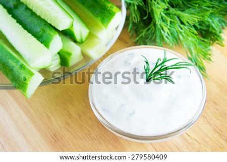 Greek Tzatziki yogurt dip (sauce) and ingredients on wooden table - stock photo