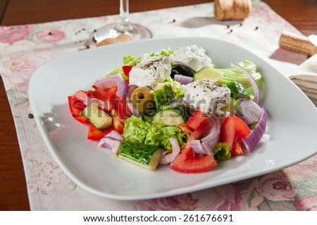 Greek Vegetable salad with feta cheese, olives, cucumbers, tomatoes,pepper  on the white plate partly - stock photo