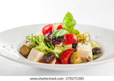 Greek Vegetable salad with feta cheese, olives, cucumbers, tomatoes, pepper  on the white plate isolated on white background - stock photo