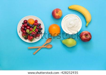 Greek yogurt around orange, banana, pear, peach, apple, plate of strawberries, raspberries, blueberries and 2 wooden spoons on blue background. Yogurt and fruits, berries as an ingredients. Top view. - stock photo
