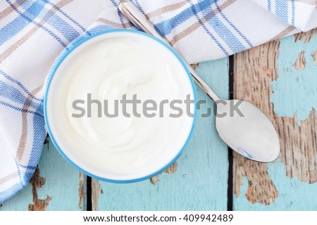 Greek yogurt in a bowl, downward view with cloth and spoon on a rustic blue wood background - stock photo