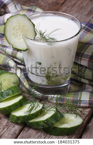 Greek yogurt with cucumber and dill close-up on the table. vertical  - stock photo