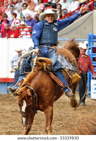 GREELEY, CO - JULY 4:  Billy Etbauer wins the saddle bronc title at the Greeley Stampede, the worlds largest Fourth of July rodeo, on July 04, 2009 in Greeley, CO.  Etbauer is a 5-time PRCA world champion. - stock photo