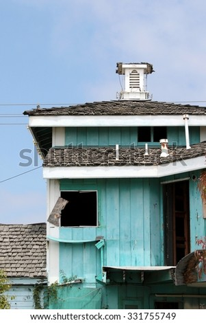 Green abandoned wooden house falling apart. - stock photo