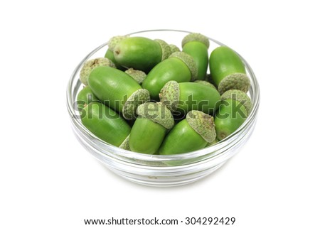 green acorns in a glass cup on a white background - stock photo
