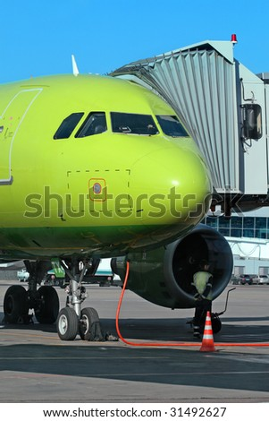 Green airplane loads fuel at the hub of international airport - stock photo