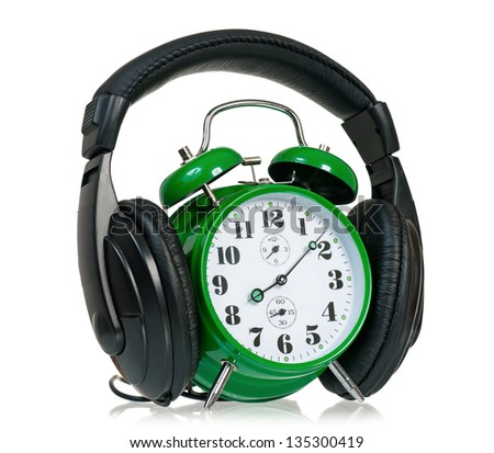 Green alarm clock with headphones, isolated on white background - stock photo