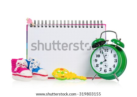 Green alarm clock with notebook and baby boots, isolated on white background - stock photo