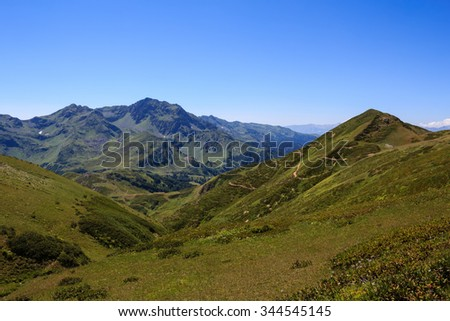 green alpine meadows and range of high rocky peaks in the valley of the caucasus mountains valley in Caucasus Mountains Abkhazia Georgia - stock photo