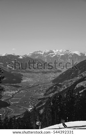 Green alpine valley and snowy mountains at horizon on a sunny spring day