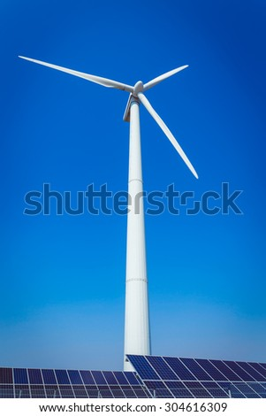Green alternative energy and environment protection ecology concept - solar battery panels and wind generator turbines against blue sky - stock photo