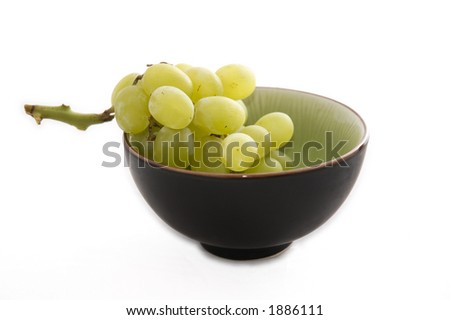 Green and black bowl full of frosty green grapes on a white background.