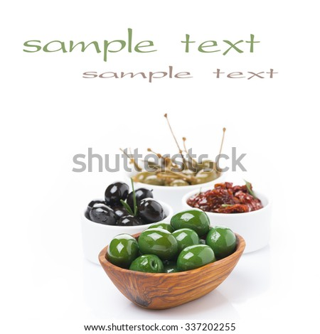 green and black olives, dried tomatoes and capers in bowls, isolated on white - stock photo