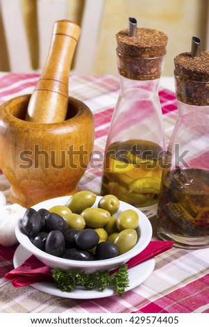 Green and black olives in a white bowl with a saucer, seasoned olive oil in glass bottles with dispenser and wooden mortar and pestle placed on the table. - stock photo