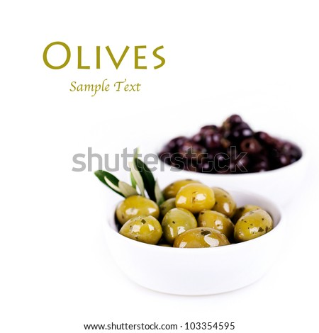 Green and black olives in a white ceramic bowl with olive branch. Isolated on white with space for text. - stock photo