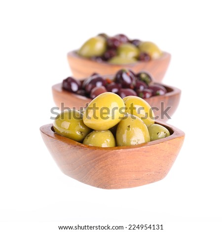 Green and black olives in white bowls over white. Intentional shallow depth of field. - stock photo
