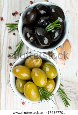 green and black olives on wooden surface - stock photo