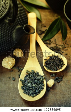 Green and black tea on wooden table - stock photo