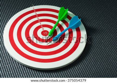 Green and blue darts arrows in the target center on wooden background. Success hitting target aim goal achievement concept background. close up. - stock photo