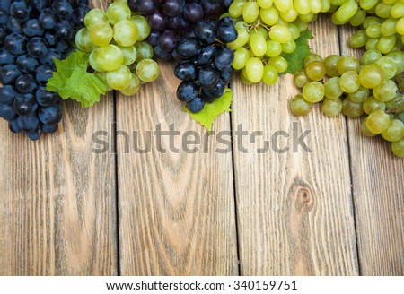 Green and blue grapes on a old wooden backgroun
