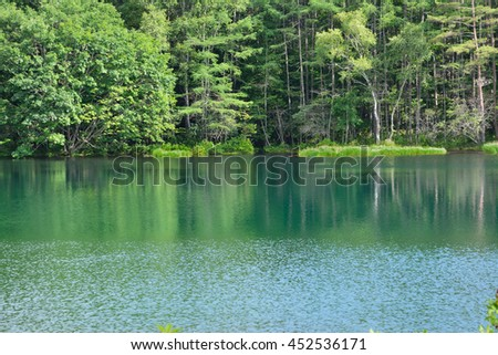 Green and blue lake in the mountain forest ( misyaka-ike in japan)