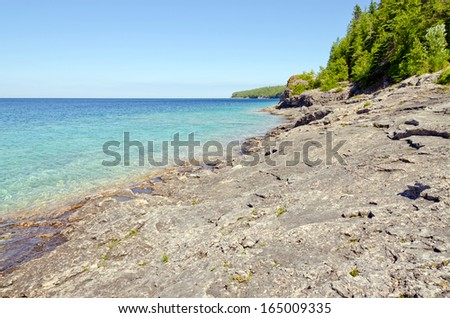 Green and blue water of Huron Lake, Ontario under blue sky. - stock photo