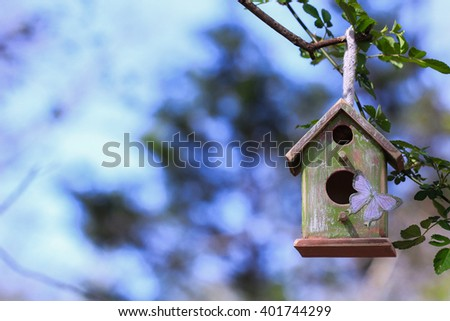 Green and brown birdhouse with purple butterfly hanging from tree branch with blurred foliage in background - stock photo