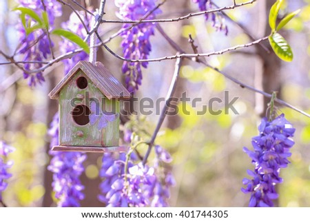 Green and brown birdhouse with purple butterfly hanging from tree branch with blurred purple spring flowers blurred in background - stock photo