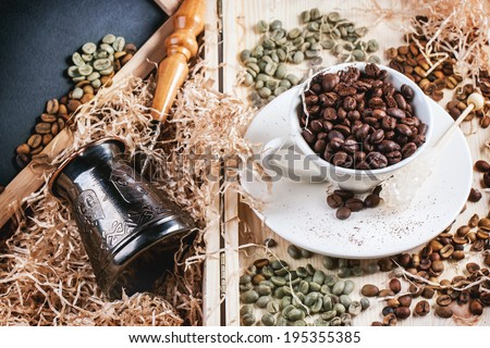Green and brown decaf unroasted coffee beans and cup of roasted coffee beans with copper cezve and black empty chalkboard in wooden box with chips. - stock photo