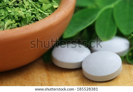Green and dired  Moringa leaves with tablet - stock photo