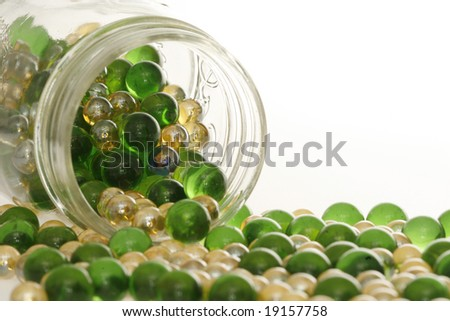 Green and Gold marbles spilling out of a jar. - stock photo