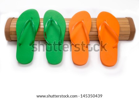 Green and orange flip flop sandals resting on bamboo mat with copy space