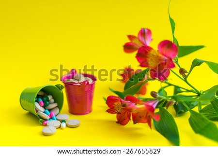 Green and pink buckets full of pills with flower at the yellow background  - stock photo