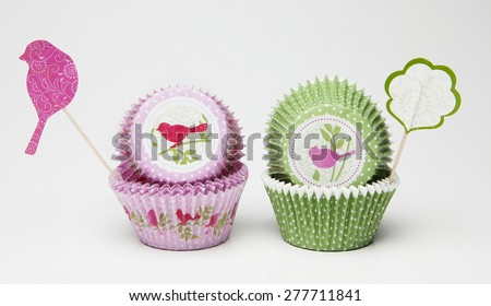 Green and Pink liners for cupcakes with bird as decoration - stock photo