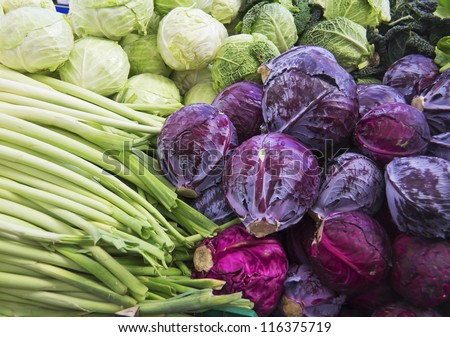 green and purple cabbage, leek on market for sale - stock photo