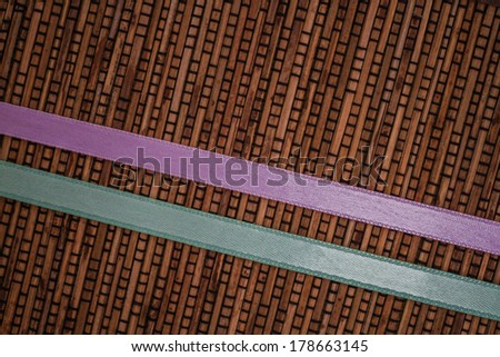 Green and purple ribbon stripes design on woven rattan background